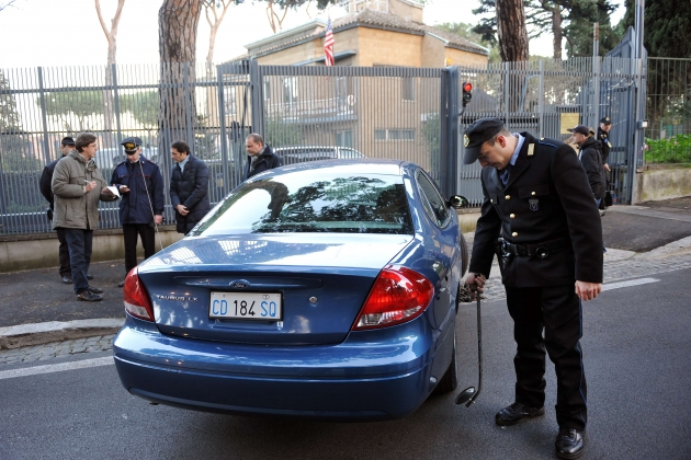 A security guard outside the U.S. Embassy to the Vatican checks for dangerous religious medals.